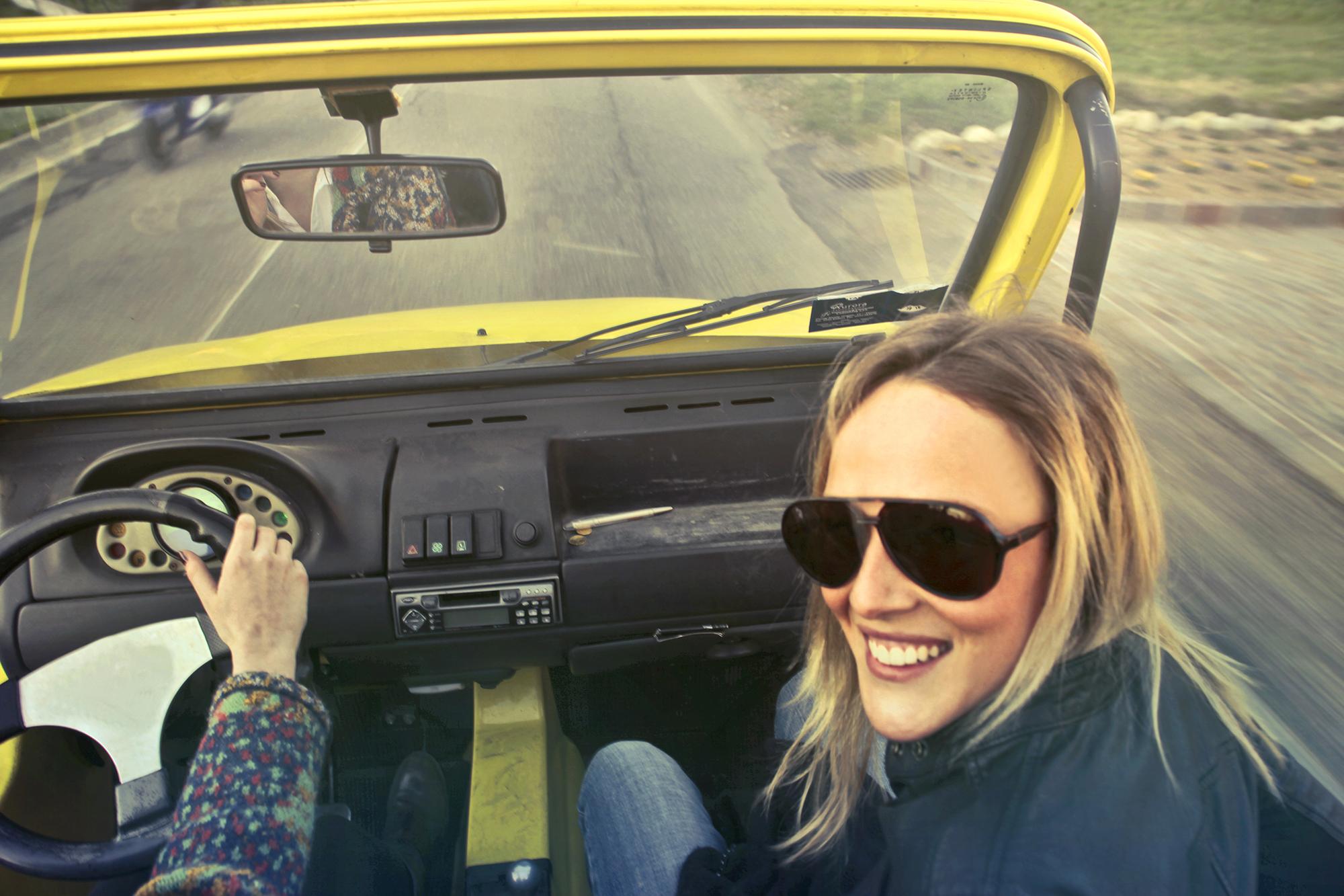 Photographie d'une femme souriante dans une voiture